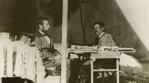 A sepia-toned photo showing Abraham Lincoln and General George McClellan seated, looking at one another, in Antietam, Maryland, circa 1862. | Episode 3 | Forever Free (1862)