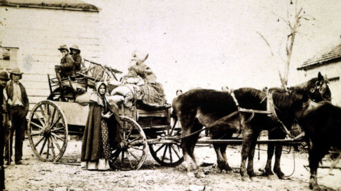 A sepia-toned photo showing a southern refugee family loading a horse-drawn wagon with their furniture and belongings. | Episode 4 | Simply Murder (1863)