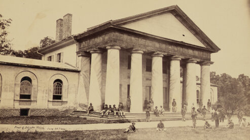 A sepia-toned photo of Union soldiers gathered outside Robert E. Lee's large home, which has grand columns outside it, in Arlington, Virginia, circa 1864. | Episode 7 | Most Hallowed Ground (1864)