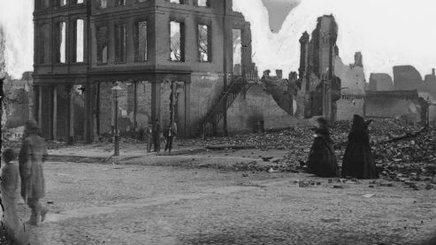 A black-and-white photo showing men and women walking past a ruined building in Richmond, Virginia, circa 1865. | Episode 8 | War Is All Hell (1865)