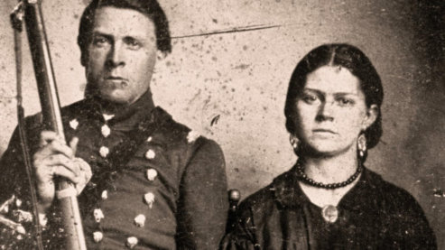 A sepia-toned photo of a man in soldier's garb posing for the photo next to a woman in a black dress, wearing a locket around her neck. The man holds a rifle upright. They both have serious expressions. | Video