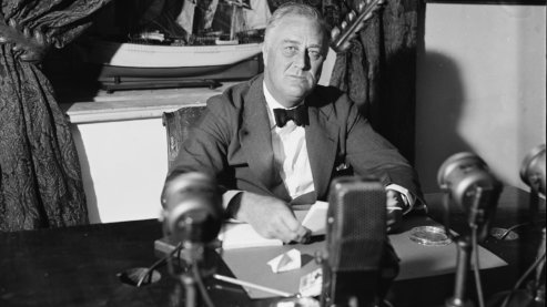 A black-and-white photo showing President Franklin Delano Roosevelt sitting behind a bank of radio microphones in the White House on September 6, 1936.   FDR's Fireside Chats